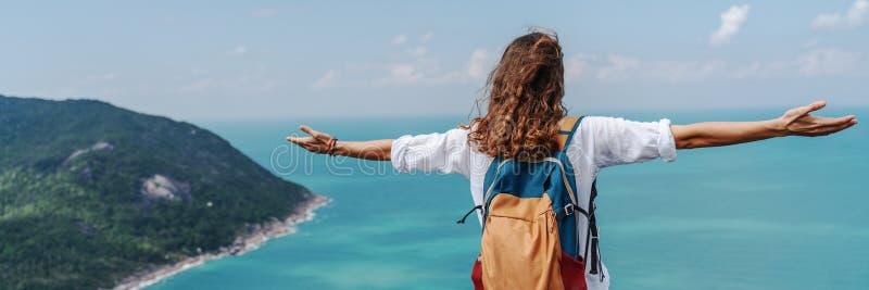 Mädchen entspannen sich auf tropischen Hügeln mit Armen offenen Feuer Freiheit mit schöner Aussicht auf das Meer von oben. Freihe stockfoto