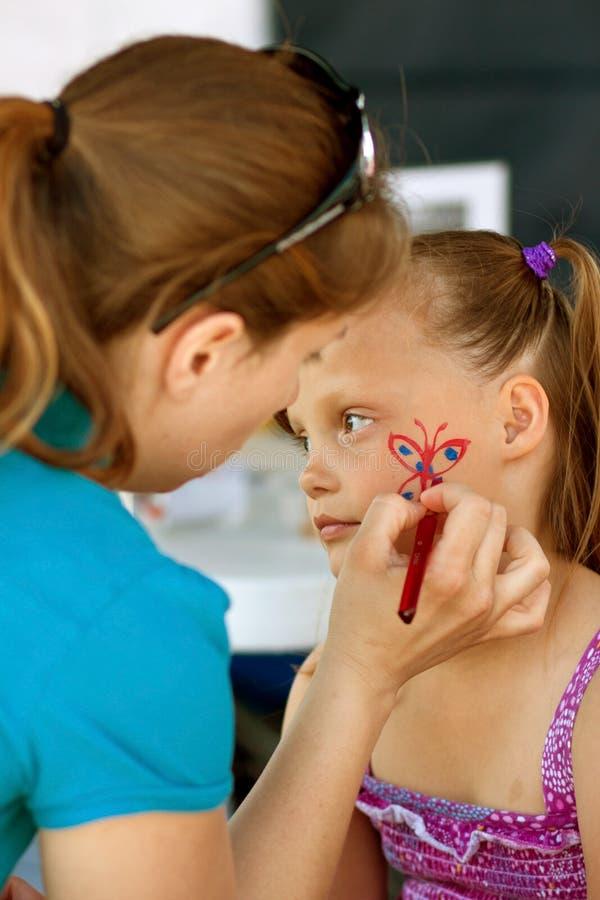 Mädchen erhält Gesicht gemalt am Festival stockfotografie