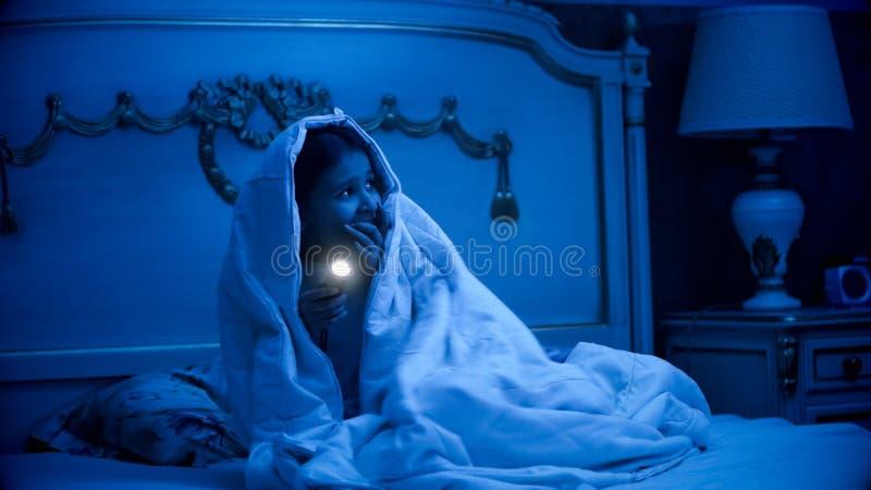 Mädchen erschrak von den Monstern, die in der Decke mit Taschenlampe bedeckt wurden lizenzfreie stockfotos