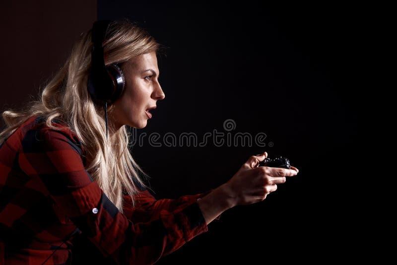 Mädchen Gamer in den Kopfhörern und mit einem Steuerknüppel, der enthusiastisch auf der Konsole spielt lizenzfreie stockfotos
