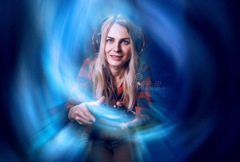 Mädchen Gamer in den Kopfhörern und mit einem Steuerknüppel in ihren Händen, welche die Netzspiele sich vorbereiten, am internati lizenzfreies stockfoto