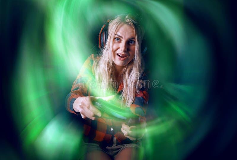 Mädchen Gamer in den Kopfhörern und mit einem Steuerknüppel in ihren Händen, welche die Netzspiele sich vorbereiten, am internati lizenzfreies stockbild