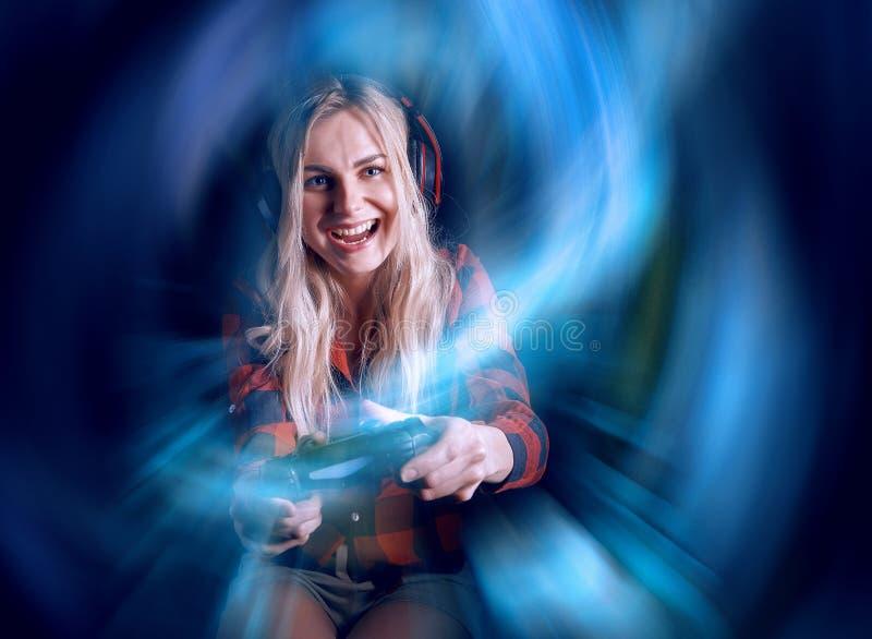 Mädchen Gamer in den Kopfhörern und mit einem Steuerknüppel in ihren Händen, welche die Netzspiele sich vorbereiten, am internati lizenzfreie stockfotos
