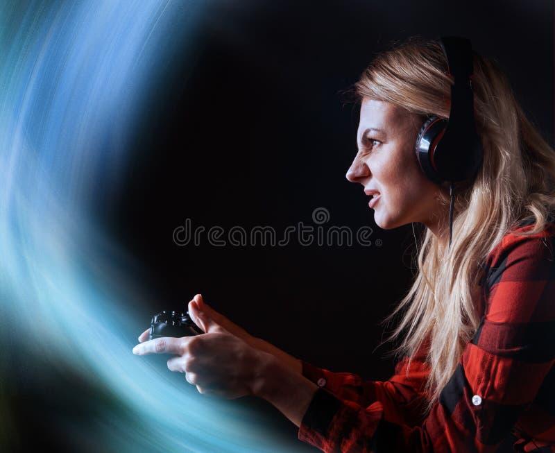 Mädchen Gamer in den Kopfhörern und mit einem Steuerknüppel in ihren Händen, welche die Netzspiele sich vorbereiten, am internati lizenzfreie stockbilder
