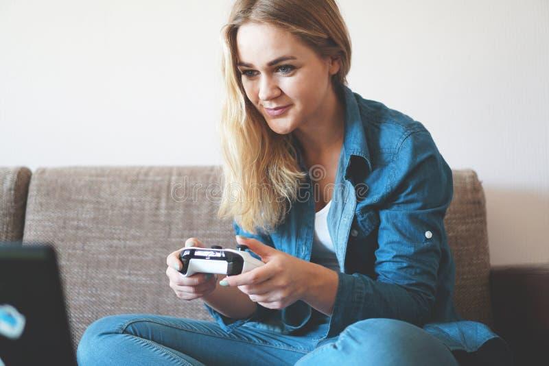 Mädchen Gamer spielt mit drahtlosem gamepad beim Betrachten des Schirmes, Videospiele lizenzfreie stockfotografie
