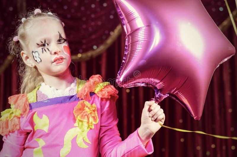 Mädchen in geformtem Ballon Clown-Costume Holding Stars lizenzfreie stockbilder