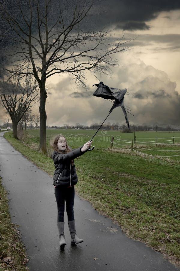 Mädchen geht mit defektem Regenschirm durch den Sturm stockfoto
