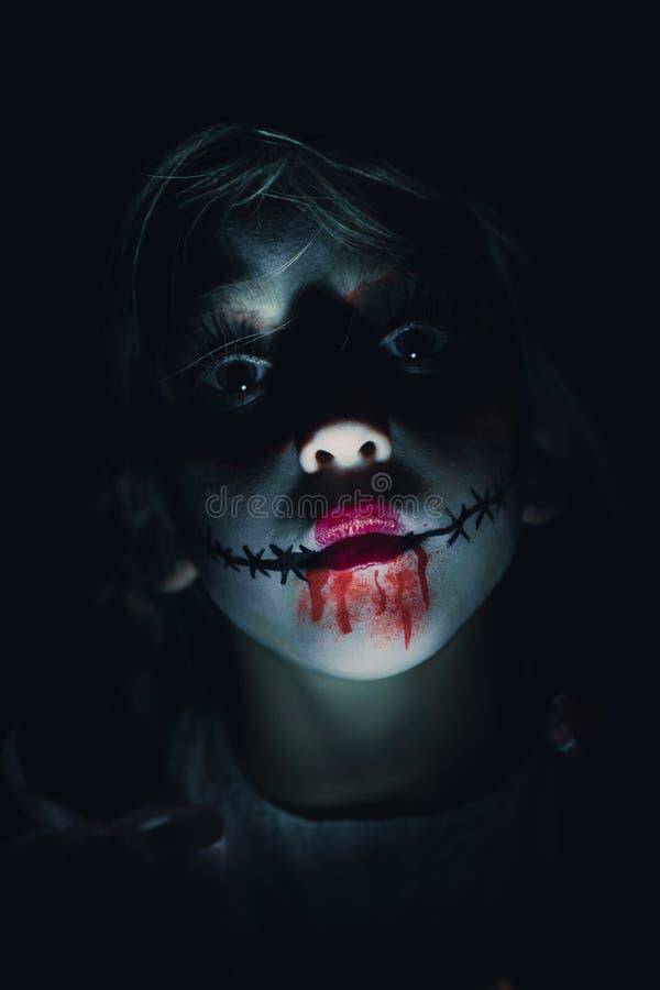 Mädchen gekleidet als Horrorpuppe für Halloween stockbild