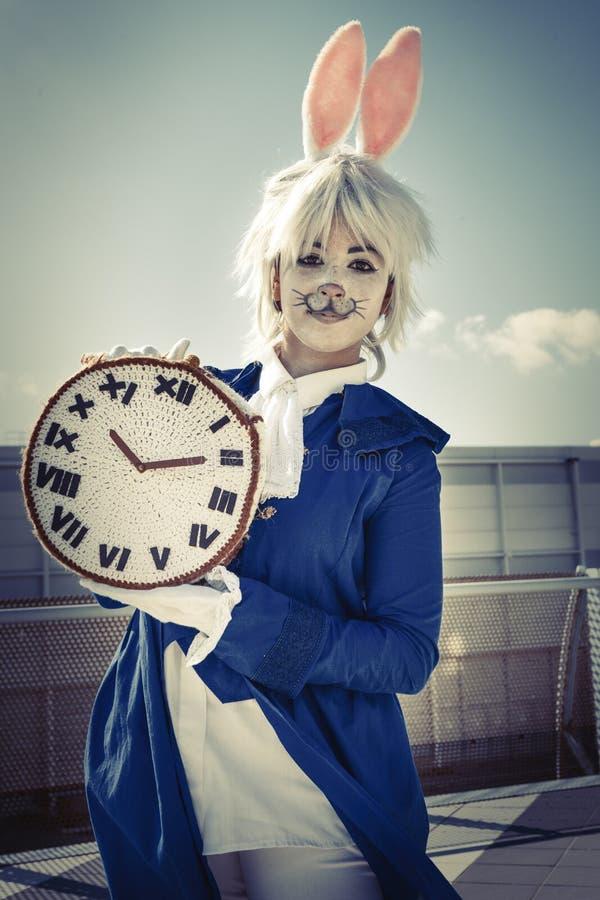 Mädchen gekleidet als Kaninchen mit Uhr lizenzfreie stockbilder