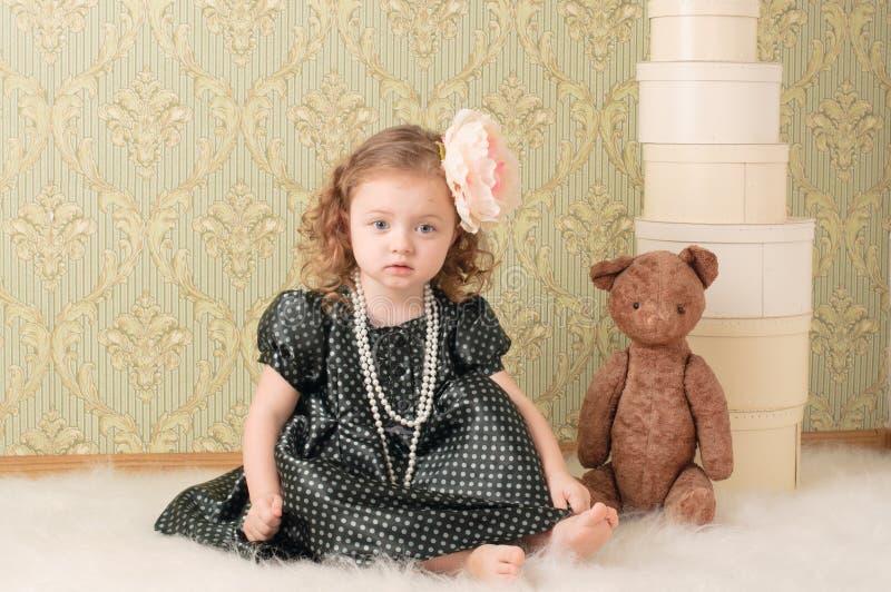 Mädchen gekleidet als Retro- Puppe stockfotografie