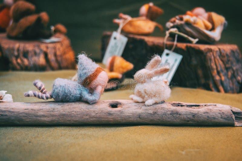 Mädchen gemacht vom Filz, der ihren Freund das Filzkaninchen betrachtet stockbild
