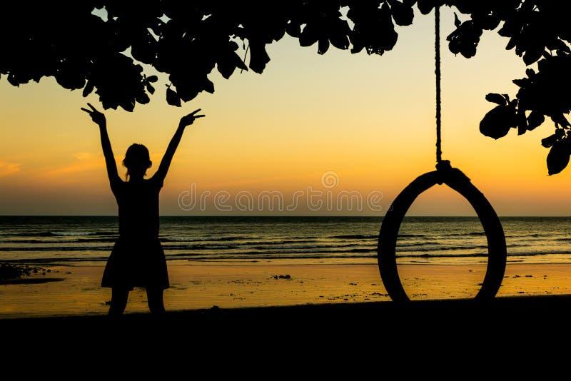 Mädchen genießt die Freiheit am Sonnenuntergangstrand lizenzfreie stockfotografie