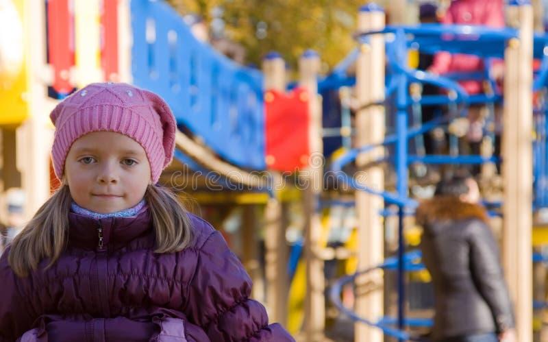 Mädchen in gestrickter Schutzkappe gegen Herbstpark lizenzfreies stockbild