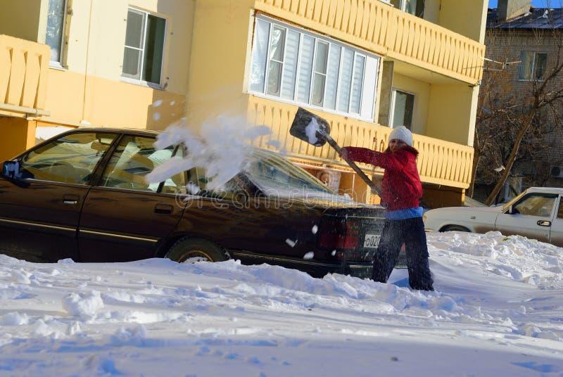 Mädchen gräbt Auto aus dem Schnee heraus stockfoto