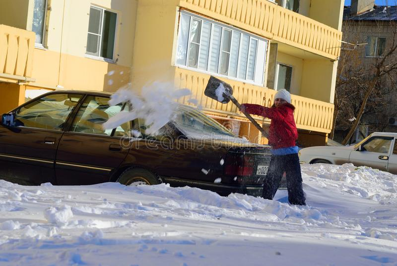 Mädchen gräbt Auto aus dem Schnee heraus stockbild