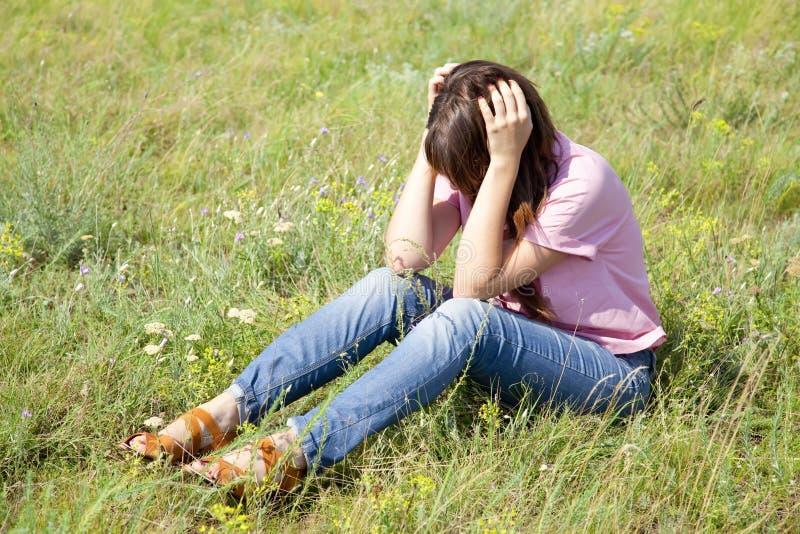 Mädchen am grünen Gras an der Landschaft. lizenzfreies stockfoto