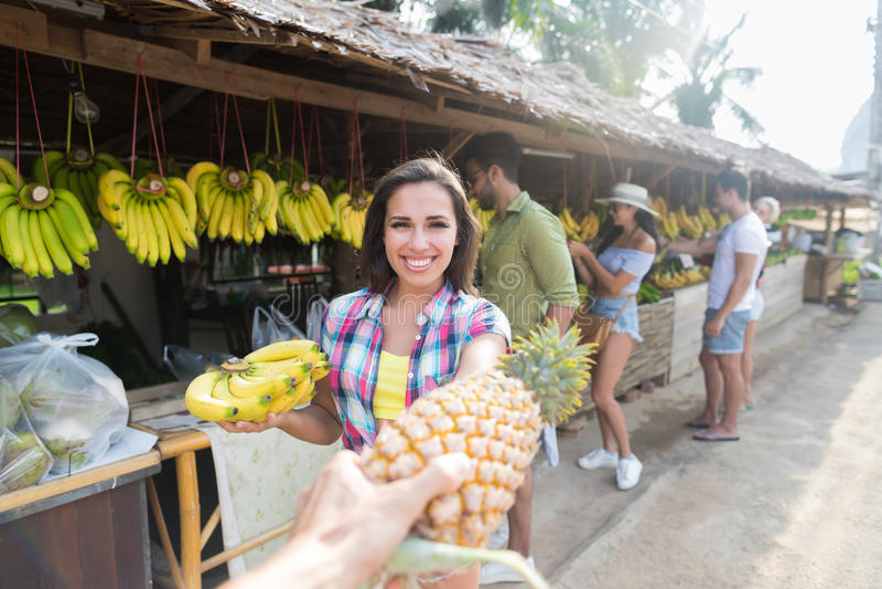 Mädchen-Griff-Bananen-Ananas-Leute-Gruppen-Asiats-Frucht-Straßenmarkt-, das neues Lebensmittel, junge Freund-Touristen exotisch k lizenzfreies stockbild
