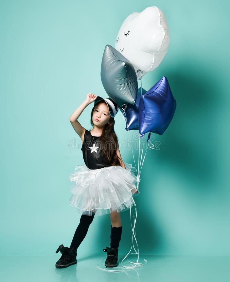 Mädchen-Griffbündel der glücklichen Mode feiern asiatisches große Heliumballone Geburtstag auf Blau stockbild