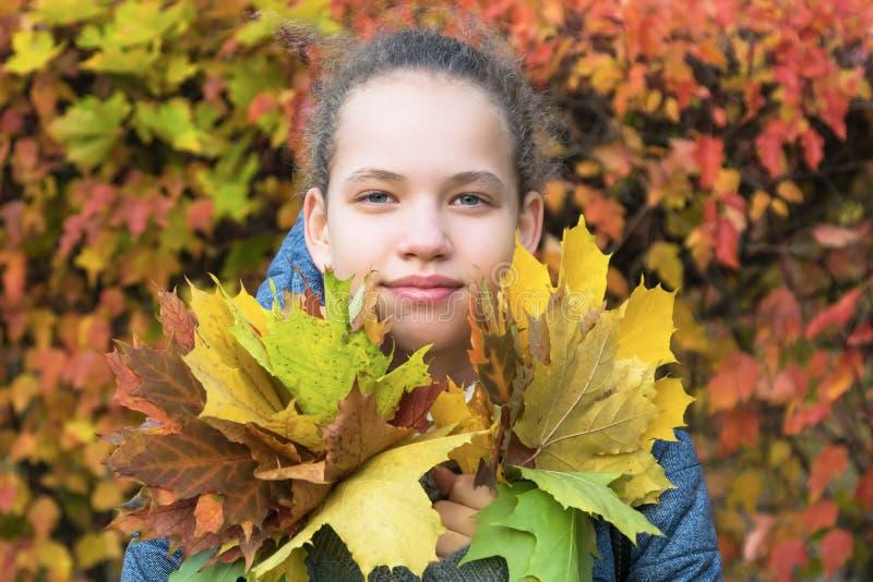 Mädchen hält Blumenstrauß in der Hand vor dem hintergrund des Herbstlaubs stockfotos