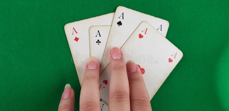 Mädchen hält Finger auf vier Spielkarten stockfotografie