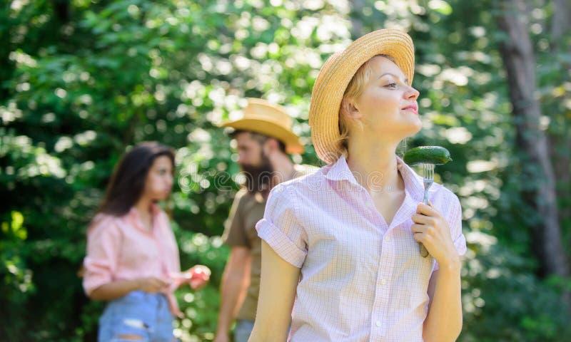 Mädchen hält Gabel mit Gurke Freunde, die Lebensmittelpicknick essen Großer Appetit der Naturzustands-Ursache Damenvegetarier her stockfotos