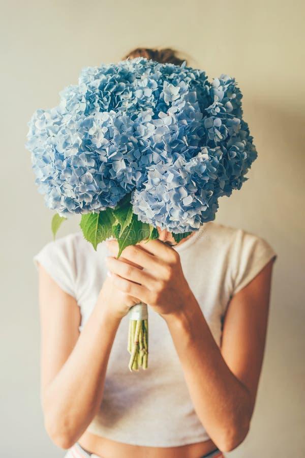 Mädchen hält vor ihr einen üppigen Blumenstrauß der blauen Hortensie lizenzfreie stockfotos