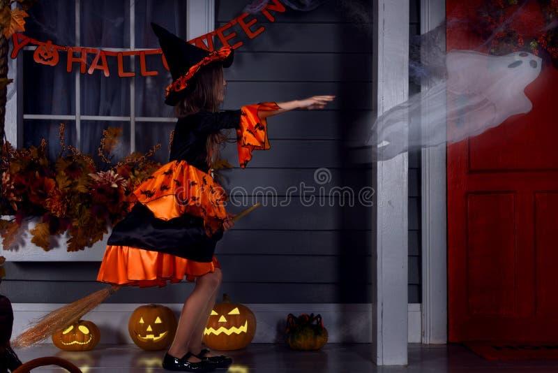 Mädchen in Halloween-Kostüm mit Besen und Geist lizenzfreie stockbilder