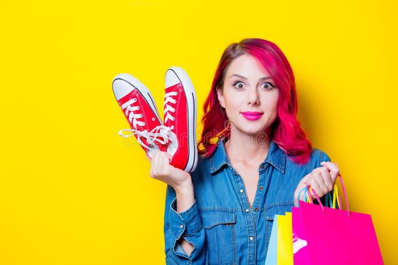 Mädchen, halten Einkaufstaschen und rote Gummiüberschuhe stockbilder