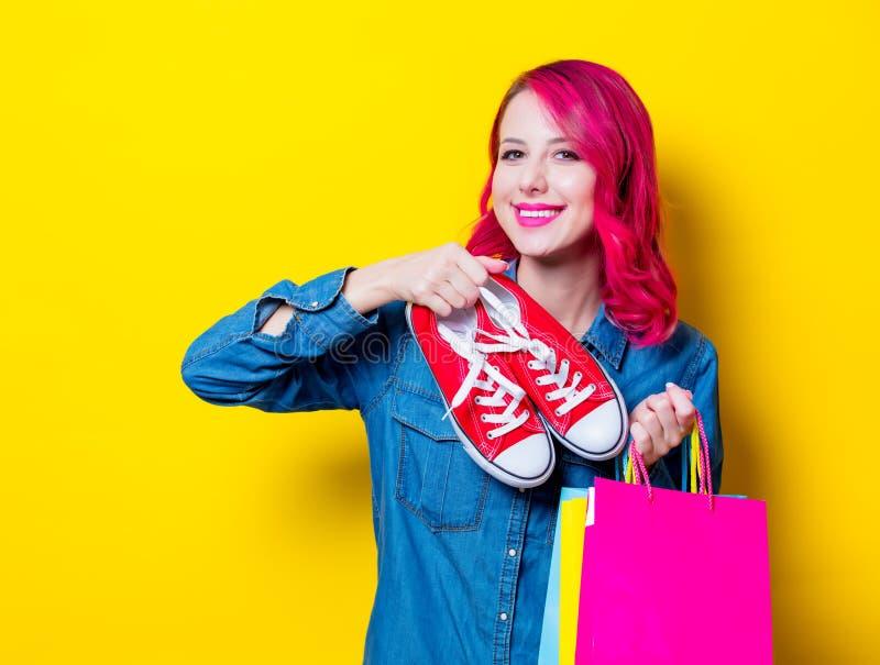 Mädchen, halten Einkaufstaschen und rote Gummiüberschuhe lizenzfreie stockfotos