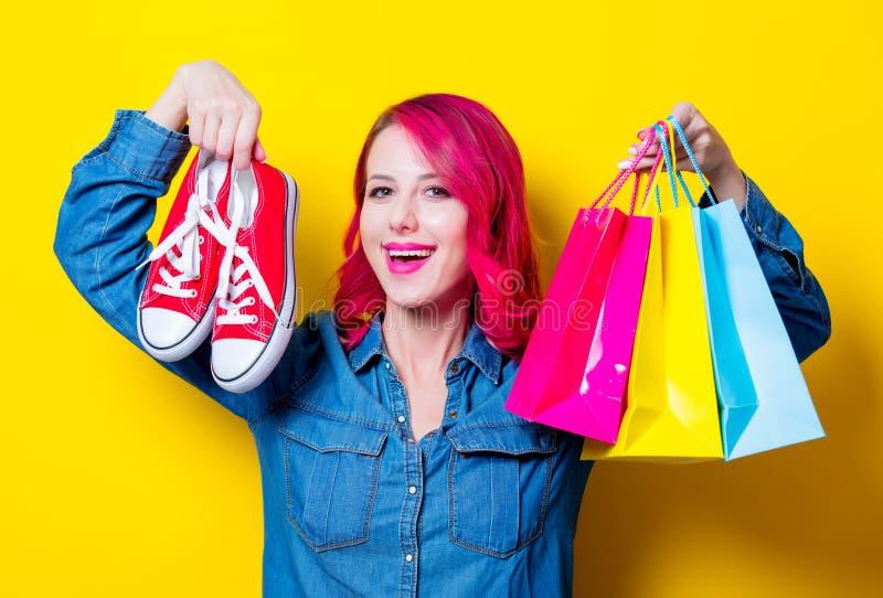 Mädchen, halten Einkaufstaschen und rote Gummiüberschuhe lizenzfreie stockfotografie