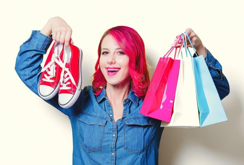 Mädchen, halten Einkaufstaschen und rote Gummiüberschuhe stockfoto