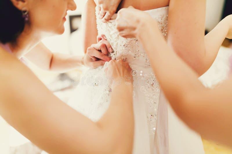 Mädchen helfen Braut, herauf ein Korsett zu knöpfen stockfotos