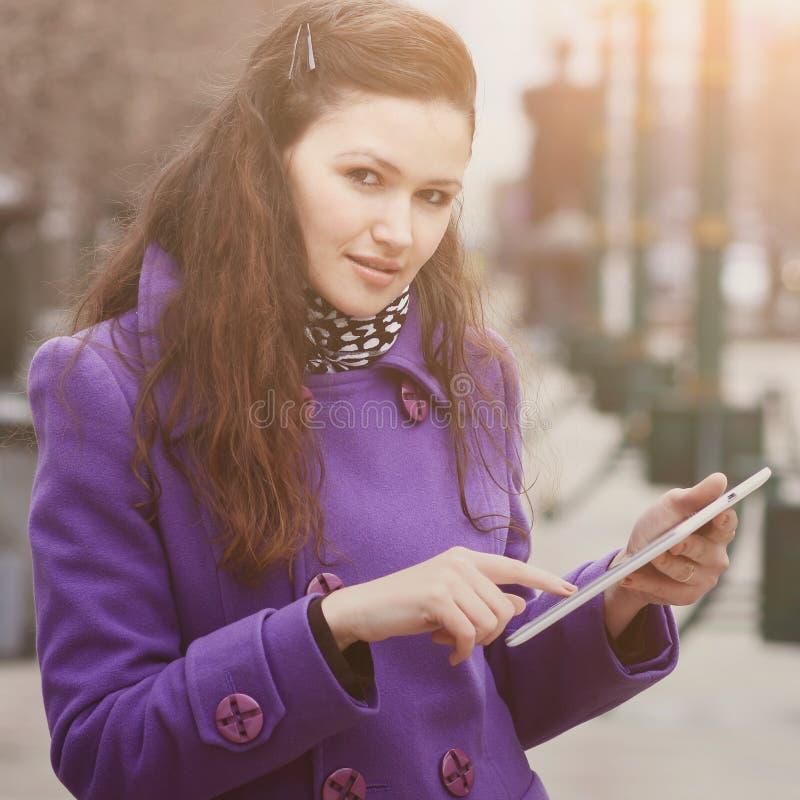 Mädchen in Herbstmantel fioletowa mit Tablette der Park stockfoto