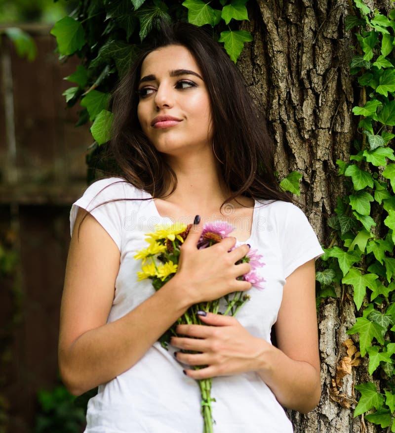 Mädchen herrlicher Brunette umarmt Blumenstraußblumen während Mageres auf Baumstamm mit Efeu Das war großes Datum Sie erhielt ihr stockfoto