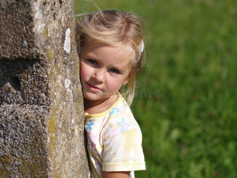 Mädchen hinter dem Steinschiffspoller lizenzfreies stockfoto