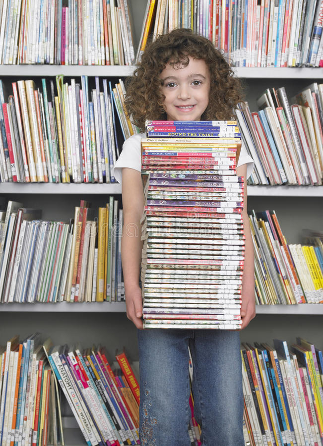 Mädchen-Holding-Stapel Bücher in der Bibliothek stockbild