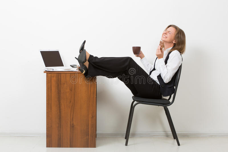 Mädchen im Büro mit seinen Füßen auf dem Tisch und lizenzfreies stockfoto