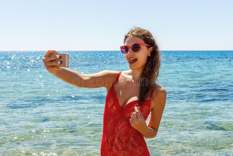 Mädchen im Badeanzug mit einem intelligenten Telefon auf dem Strand Mädchen, das Spaß selfie am Strand nimmt lizenzfreie stockbilder