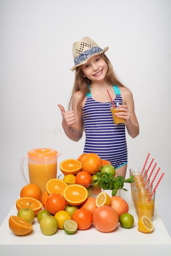 Mädchen im Badeanzug und im Sommerhut mit vielen Zitrusfrüchten und Orangensaft stockbild