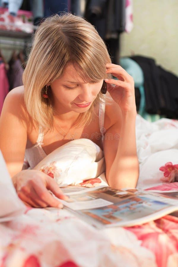 Mädchen im Bett sprechend am Telefon beim Lesen lizenzfreies stockbild