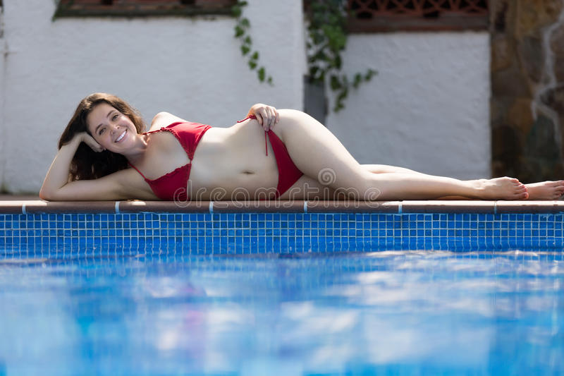 Mädchen im Bikini, der nahe Pool stillsteht lizenzfreie stockbilder