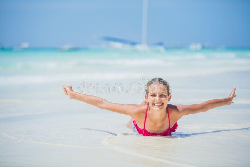 Mädchen im Bikini, der Spaß auf tropischem Strand liegt und hat stockbilder