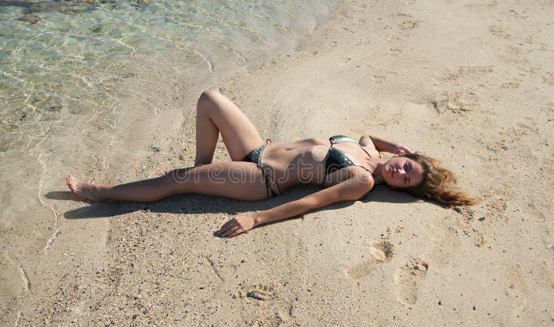 Mädchen im Bikini ein Sonnenbad nehmend am Strand lizenzfreie stockfotos