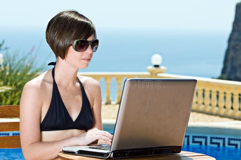 Mädchen im Bikini unter Verwendung ihres LaptopPoolside lizenzfreie stockfotografie