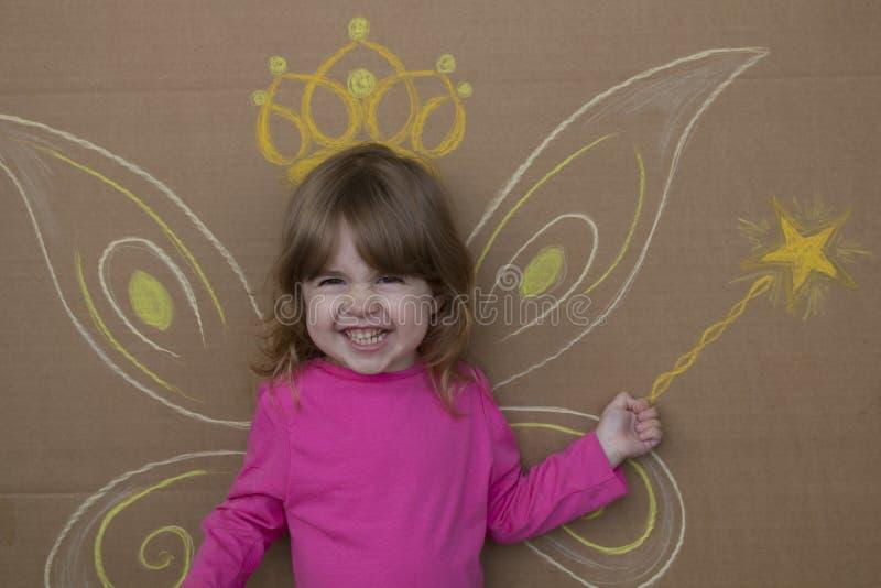 Mädchen im Bild von Feen mit gemalten Flügeln und magischen dem Stab, die gegen die Wand sitzt lizenzfreies stockfoto