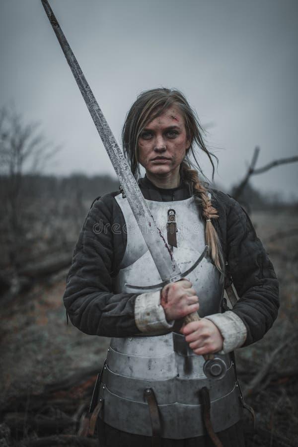 Mädchen im Bild von ` Jeanne d Bogen in der Rüstung und mit Klinge in ihren Händen steht auf Wiese Rückseitige Ansicht lizenzfreie stockfotos