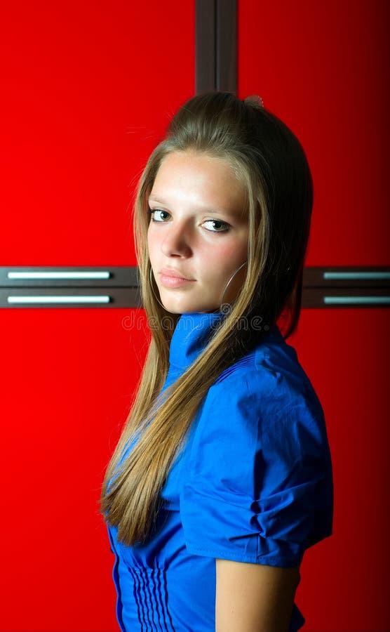 Mädchen im Blau am roten Hintergrund lizenzfreies stockbild