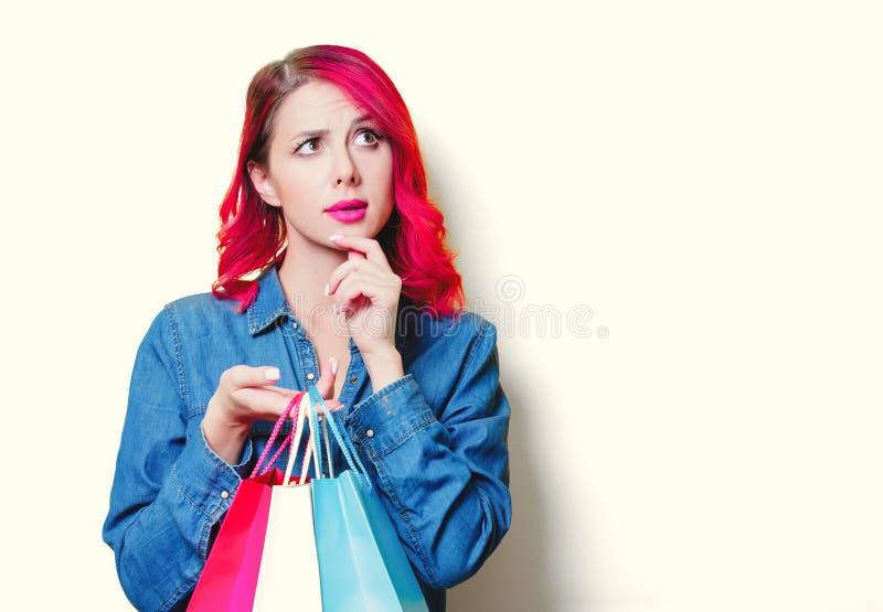 Mädchen im blauen Hemd, halten farbige Einkaufstaschen lizenzfreies stockfoto