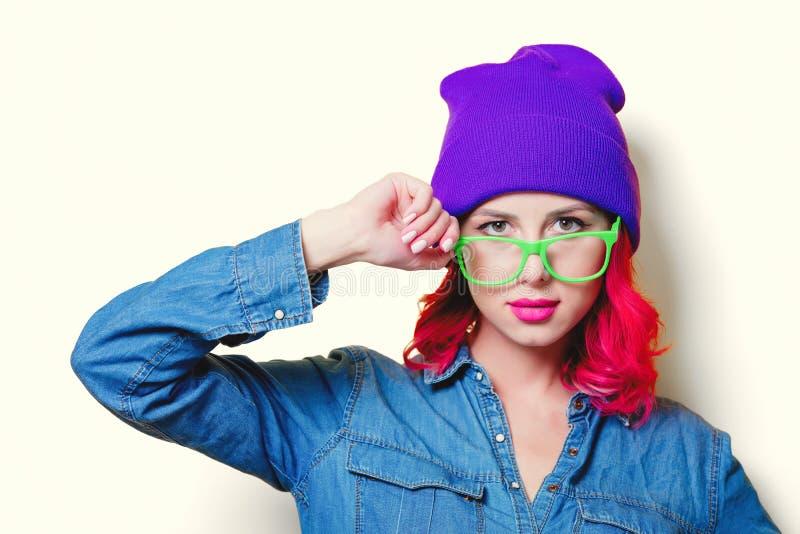Mädchen im blauen Hemd, im purpurroten Hut und in den grünen Gläsern stockbild