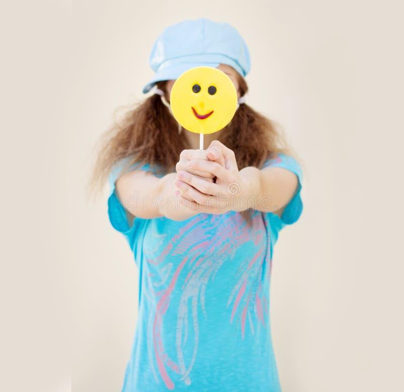 Mädchen im blauen Hemd und in der Kappe mit zwei Endstücken hält vor einer großen gelben Süßigkeit lizenzfreies stockbild